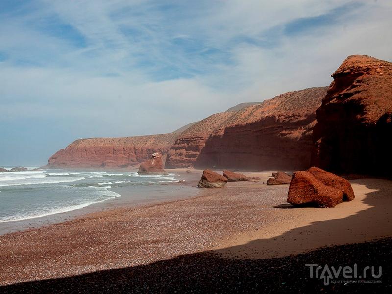 Скалы на пляже Легзира в Марокко отливают металлическими оттенками отражающейся от океана синевы / Марокко