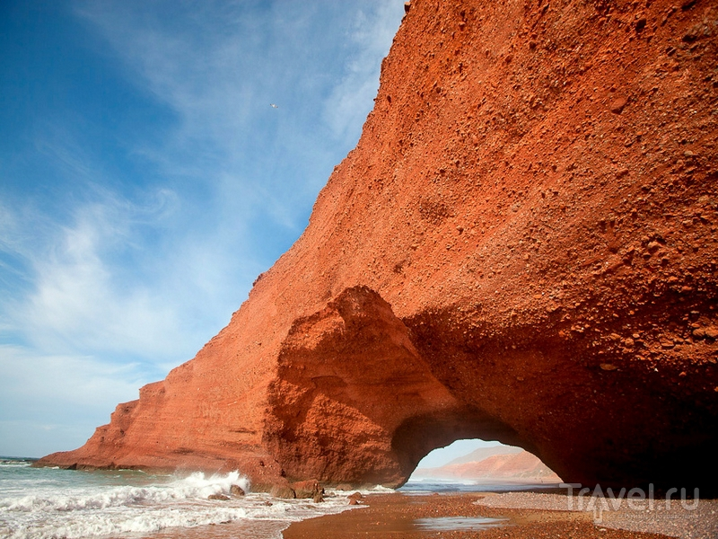 Насыщенные оранжевые и терракотовые оттенки скал на пляже Легзира в Марокко / Марокко