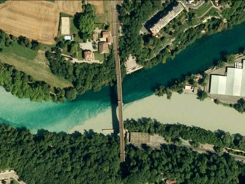 Стрелка, где соединяются мощные потоки, передает контрастные оттенки двух горных рек, Швейцария / Швейцария
