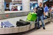 Упакованный в пленку чемодан заметен на багажной ленте